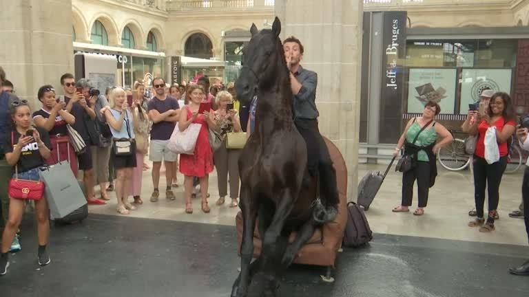 法國巴黎某個火車站,21日出現「馬上」藝術快閃演出,兩名演出者坐在馬背上,在車站...