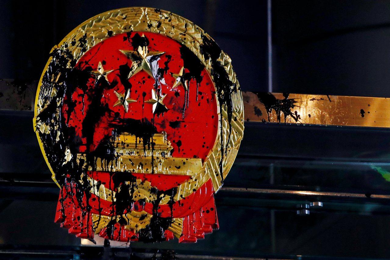 香港中聯辦大樓外的中國大陸國徽21日深夜被示威者塗汙。(路透)