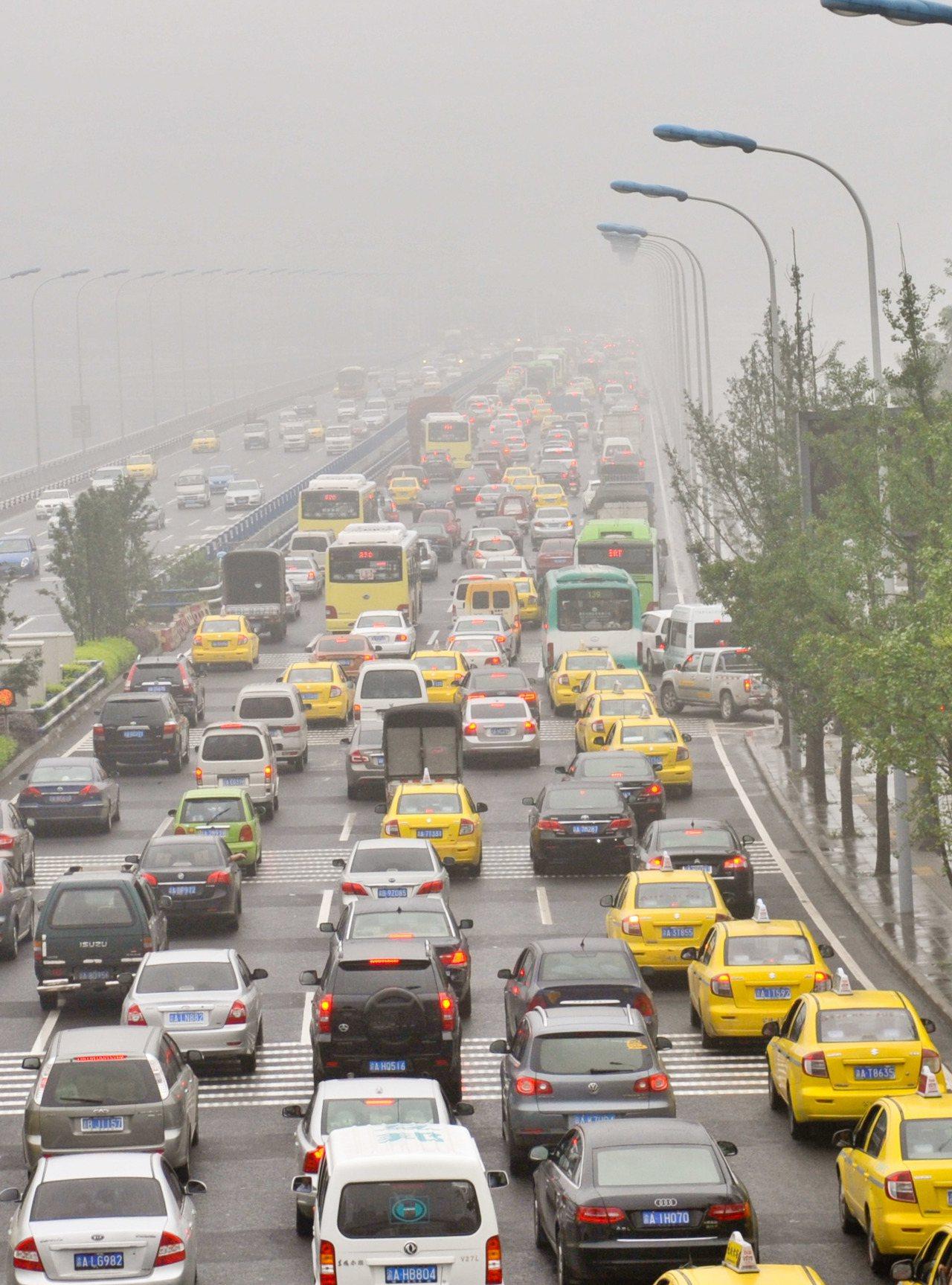 圖為重慶主城區嘉華大橋上,汽車在雨霧中緩慢行駛。 新華社