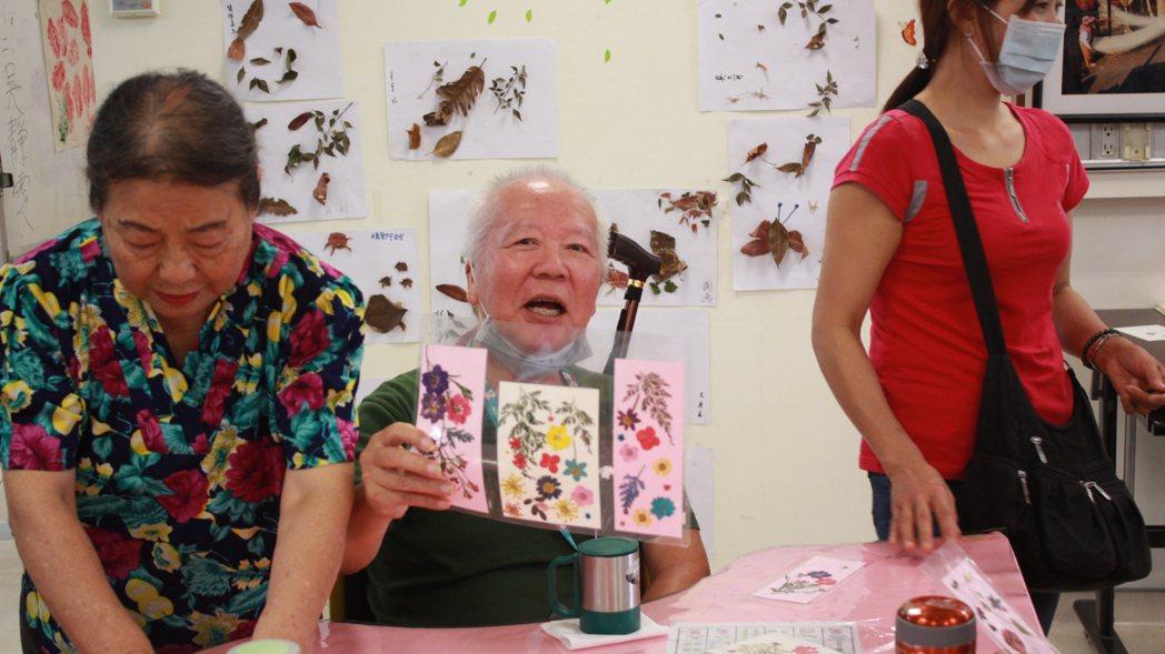 蘇黃美在新北市立聯合醫院板橋院區陽光學堂擔任志工,耐心陪伴失智長者製作乾燥花。 ...
