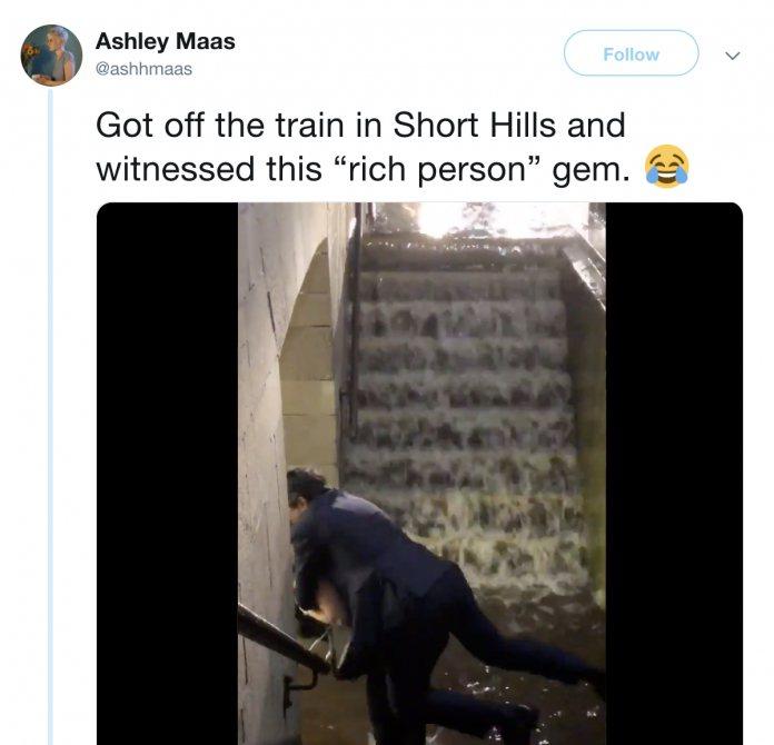 男子站在入口前,似乎不想弄濕自己,突然一名女子從旁邊出現將男子背走。圖擷自Ashley Maas 推特