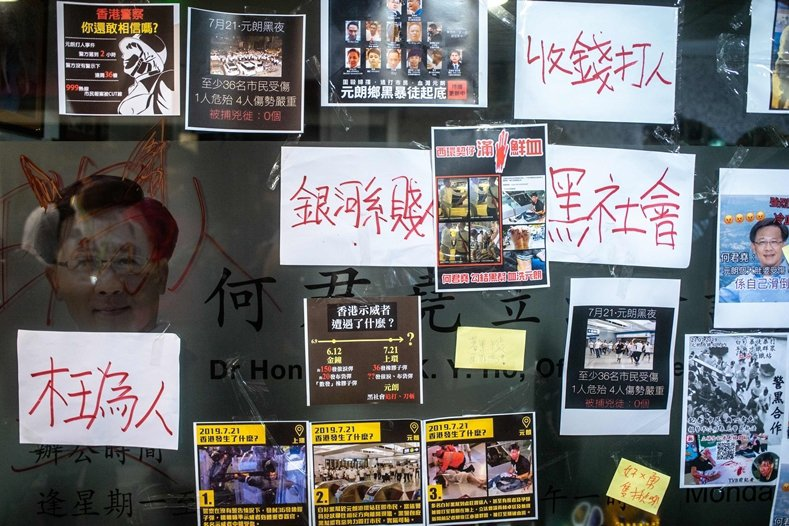 香港建制派議員何君堯被目擊與白衣人握手引發民眾不滿。其位於荃灣的服務處遭人貼滿抗議標語與塗鴉。 圖/美聯社