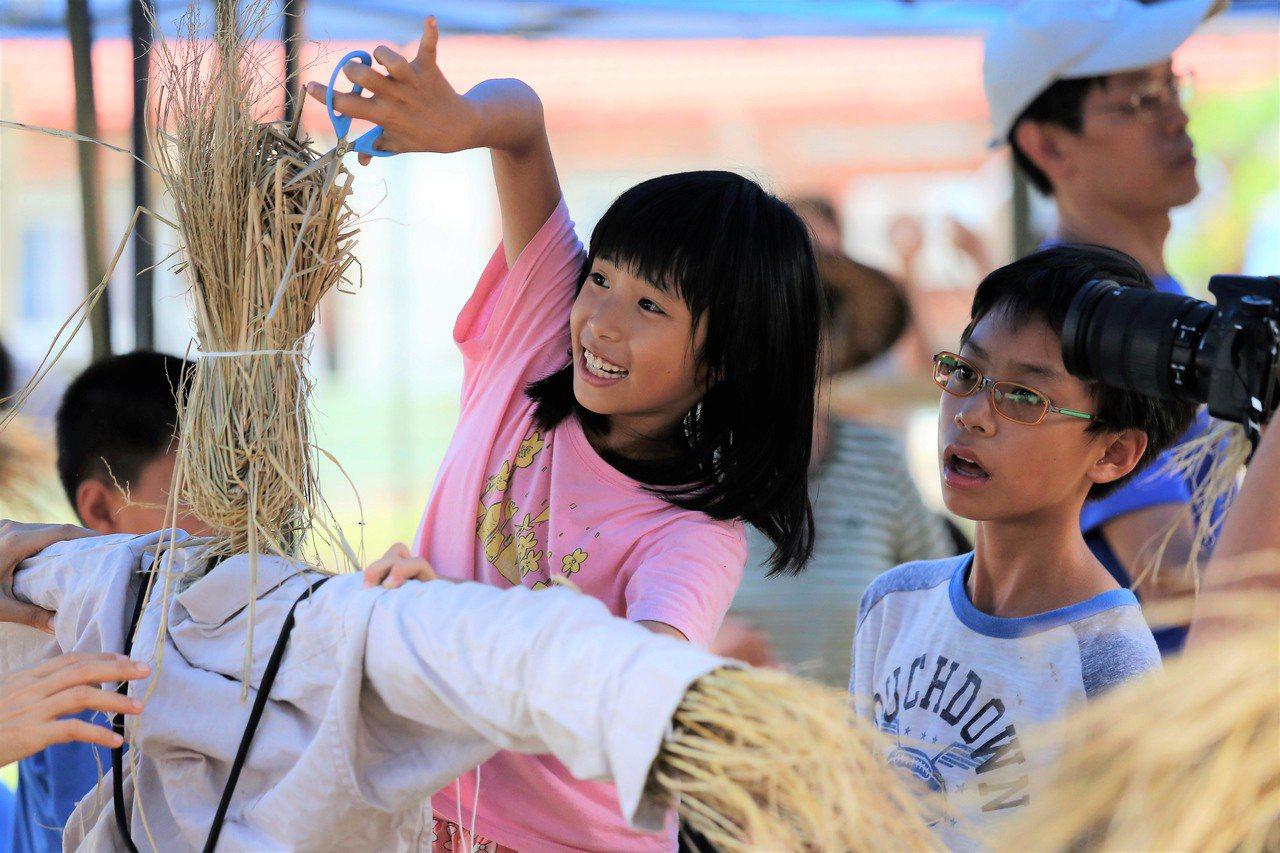 南臺科大團隊與在地社區結合共推農事體驗,小朋友開心學做稻草人。圖/南臺科大團隊提...