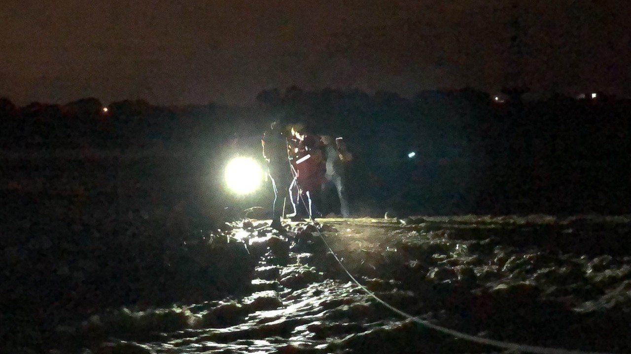 釣客受困溪水暴漲的沙洲,台中市消防局搜救人員漏夜搜救男釣客脫困。圖/台中市政府消...
