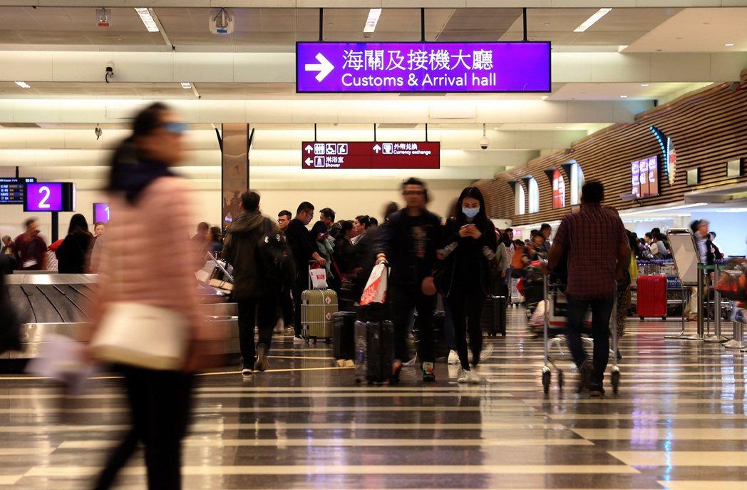 圖為搭機抵達台灣的旅客,通過桃園機場第一航廈入境海關檢查室準備提領托運行李。 報...