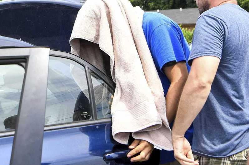 關執法局探員到田納西州逮捕無證移民時,遭遇社區居民抵抗長達四小時。圖為 一名男子蒙著頭被押進汽車。 (美聯社)