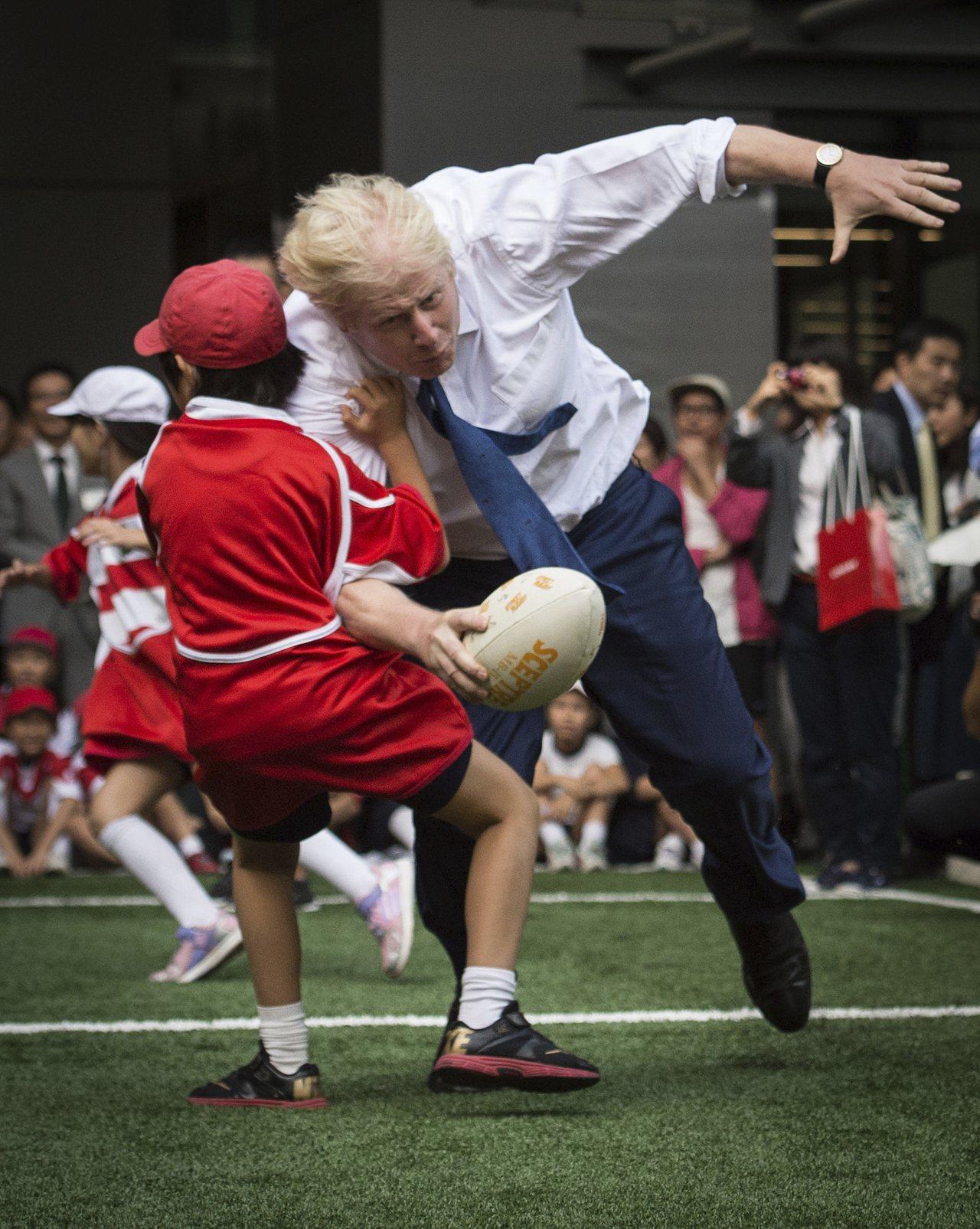下任英國首相強生行事率性,不顧形象。圖為2015年他訪問日本,在東京街頭與學童玩...