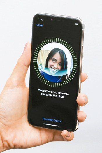 圖為消費者使用iPhone X的臉部辨識功能。路透