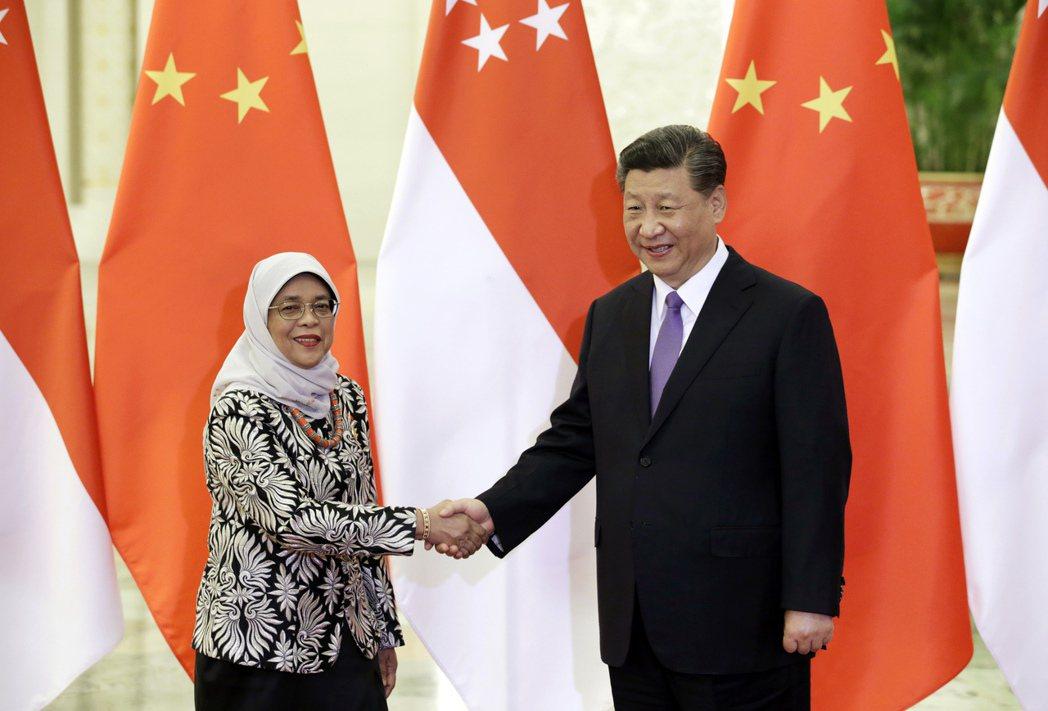習近平提出「中國夢」,積極加強對海外僑民的統戰。圖為習近平與新加坡總統哈莉瑪.雅各布。 圖/美聯社