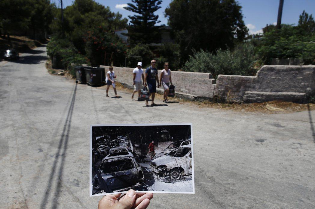 一家人悠閒經過的大街上,在一年前曾排滿了被野火燒毀的汽車。 圖/歐新社