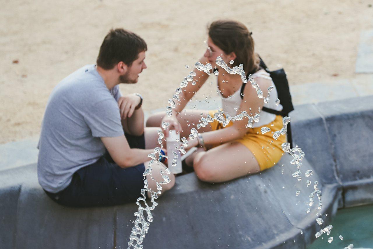 比利時24日出現攝氏38.9度高溫,刷新該國紀錄,圖為兩名在布魯塞爾市區一處噴泉...