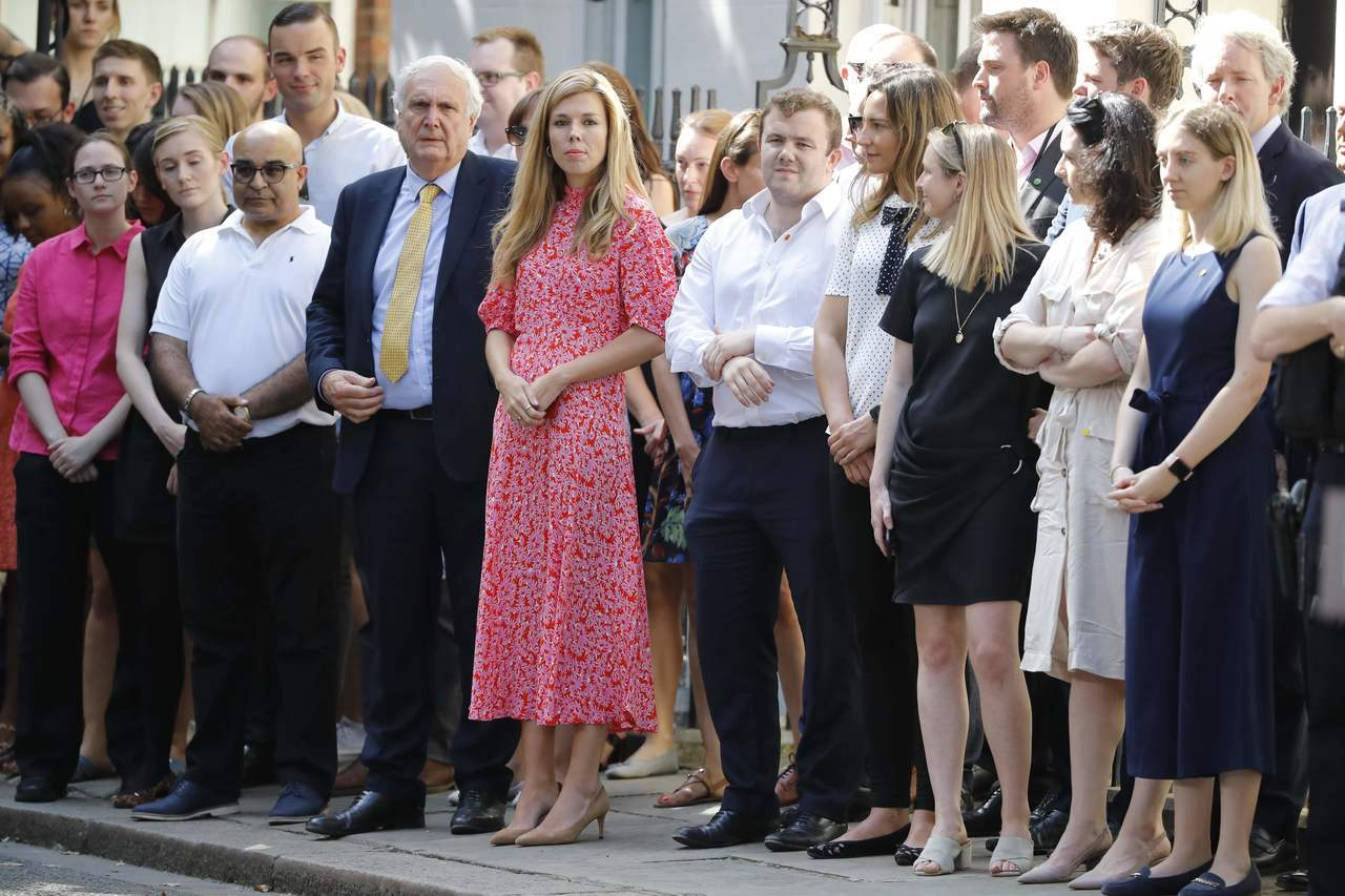 強生的女友席孟茲(中穿紅衣者)24日在首相官邸前亮相,迎接強生一起搬進官邸。 (...