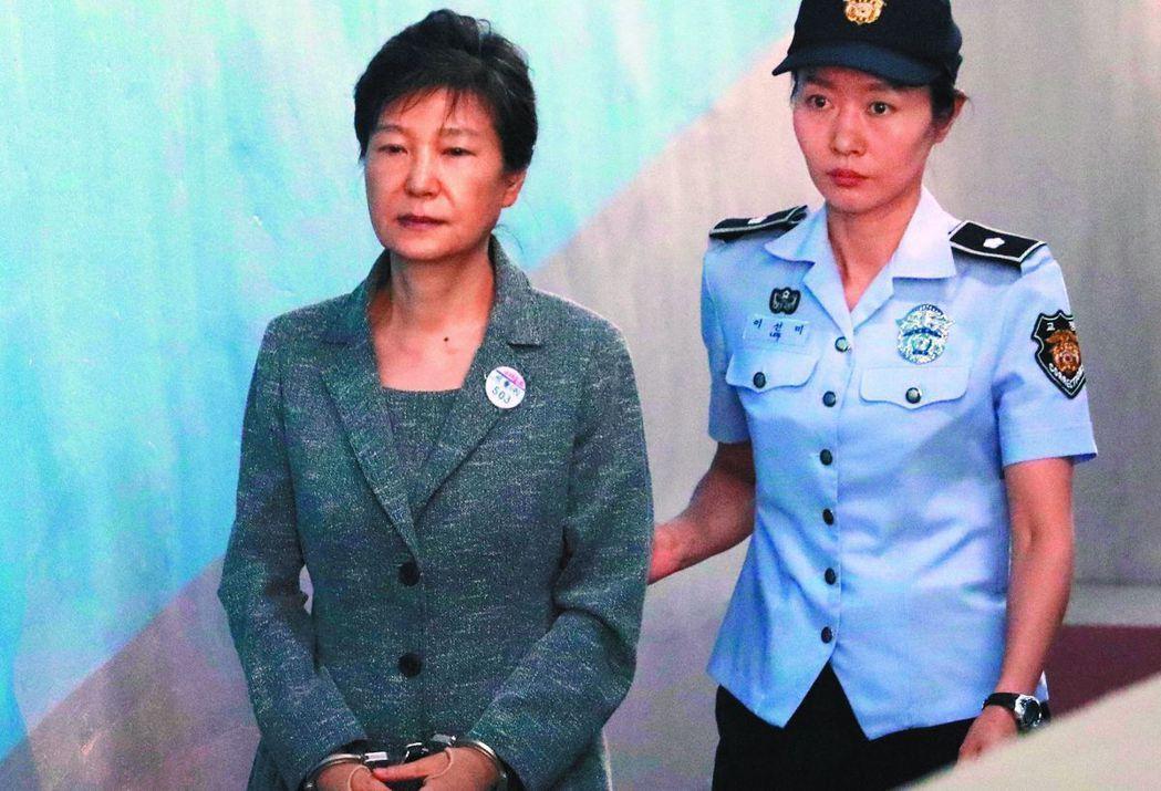 南韓前總統朴槿惠(左)因濫權、收賄等十六項罪名,被判處廿四年有期徒刑。圖為她去年...