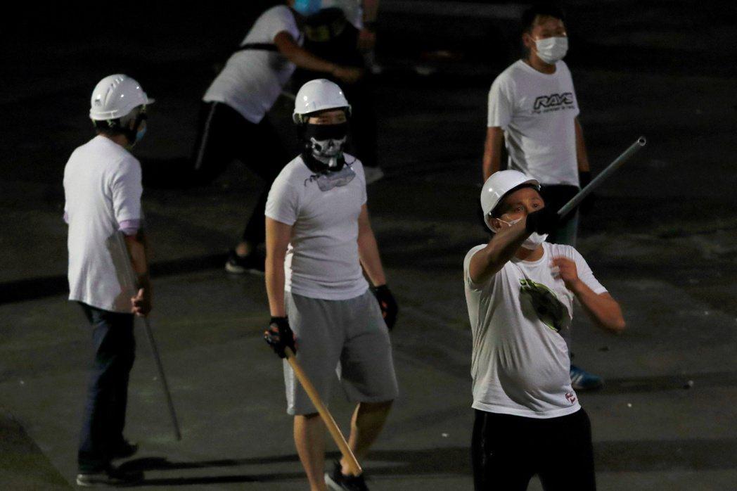 香港立法會議員何君堯在當晚被目擊與白衣人「握手寒暄、親切點讚」。圖為7月21日手持棍棒的白衣人。 圖/路透社