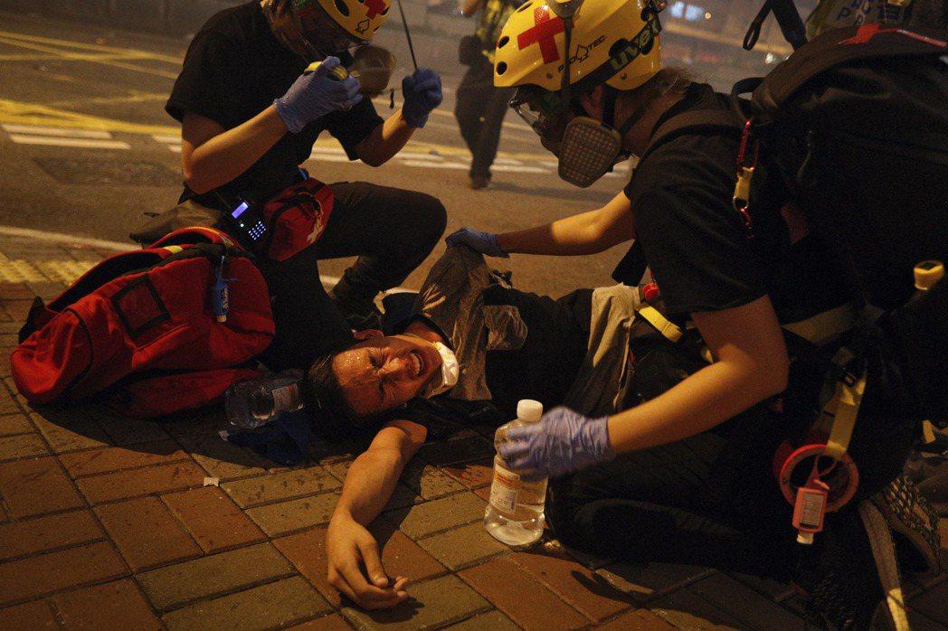 警方發射多枚催淚彈,示威者用生理鹽水替同伴清洗眼睛。 圖/美聯社