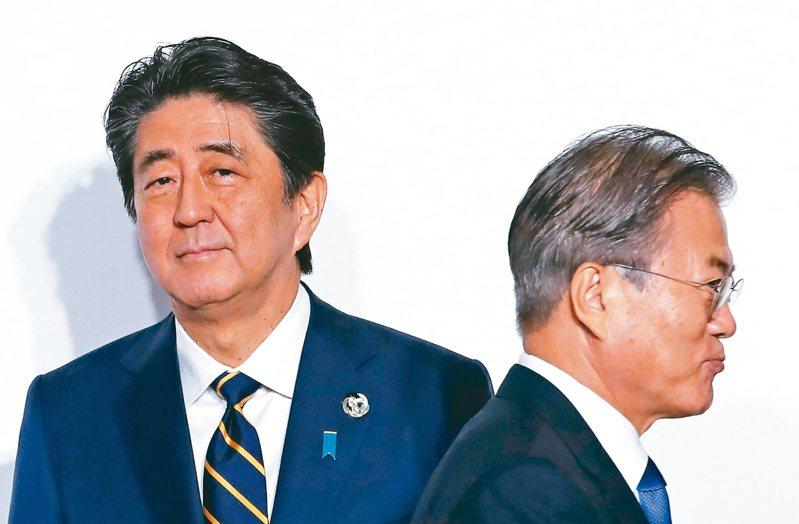 日本加強對原料出口到南韓的管制,使兩國關係緊張。圖為日本首相安倍晉三(左)與南韓總統文在寅(右),六月廿八日在日本大阪G20峰會上準備合影。 (美聯社)