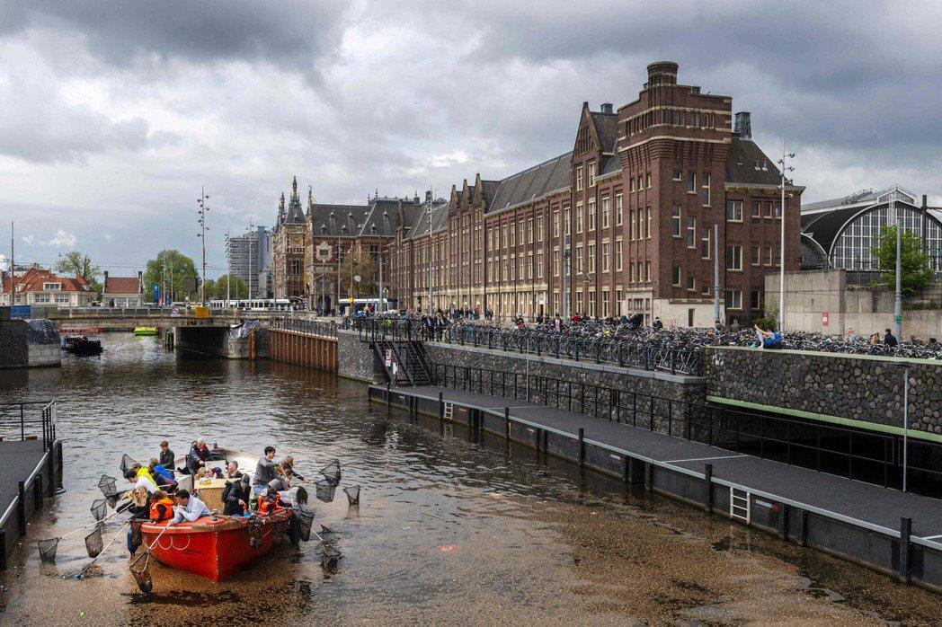 塑膠鯨魚遊船乘客在阿姆斯特丹運河裡打撈塑膠垃圾。(法新社)