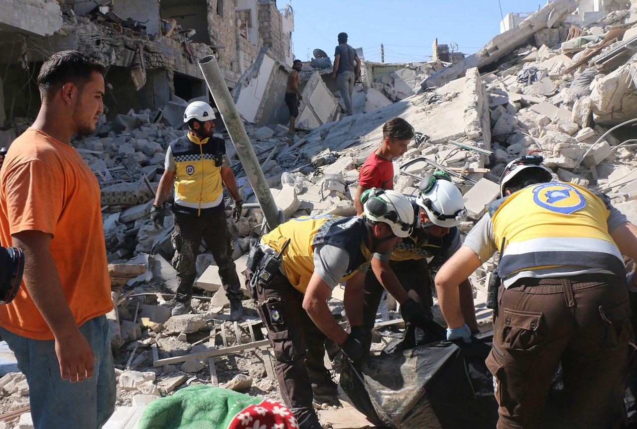 敘利亞民防工作人員在房屋廢墟下搜尋傷亡民眾。 美聯社