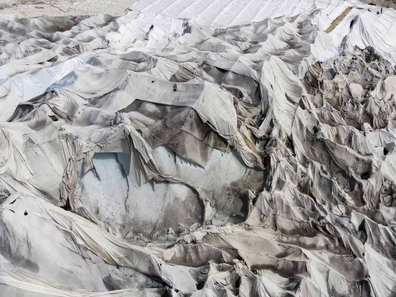 當地居民在冰川上架設白布。歐新社