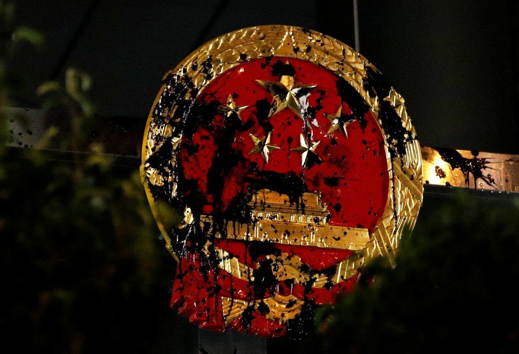 7月21日反送中上街,陳抗民眾向中聯辦中國徽丟擲黑漆。 圖/路透社
