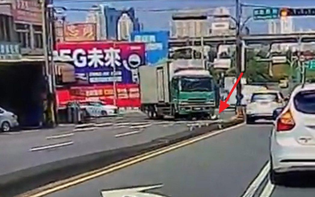 張姓女機車騎士(紅色箭頭處)險遭大貨車輾過,拼命在車前掙扎爬出。圖/翻攝自網路