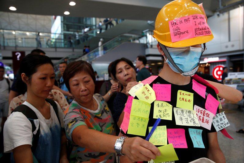 香港機場入境大廳昨天發動靜坐抗議元朗暴力事件,一名示威者身上被同伴貼上抗議便利貼,作為「連儂牆」運動的一部分。 (路透)