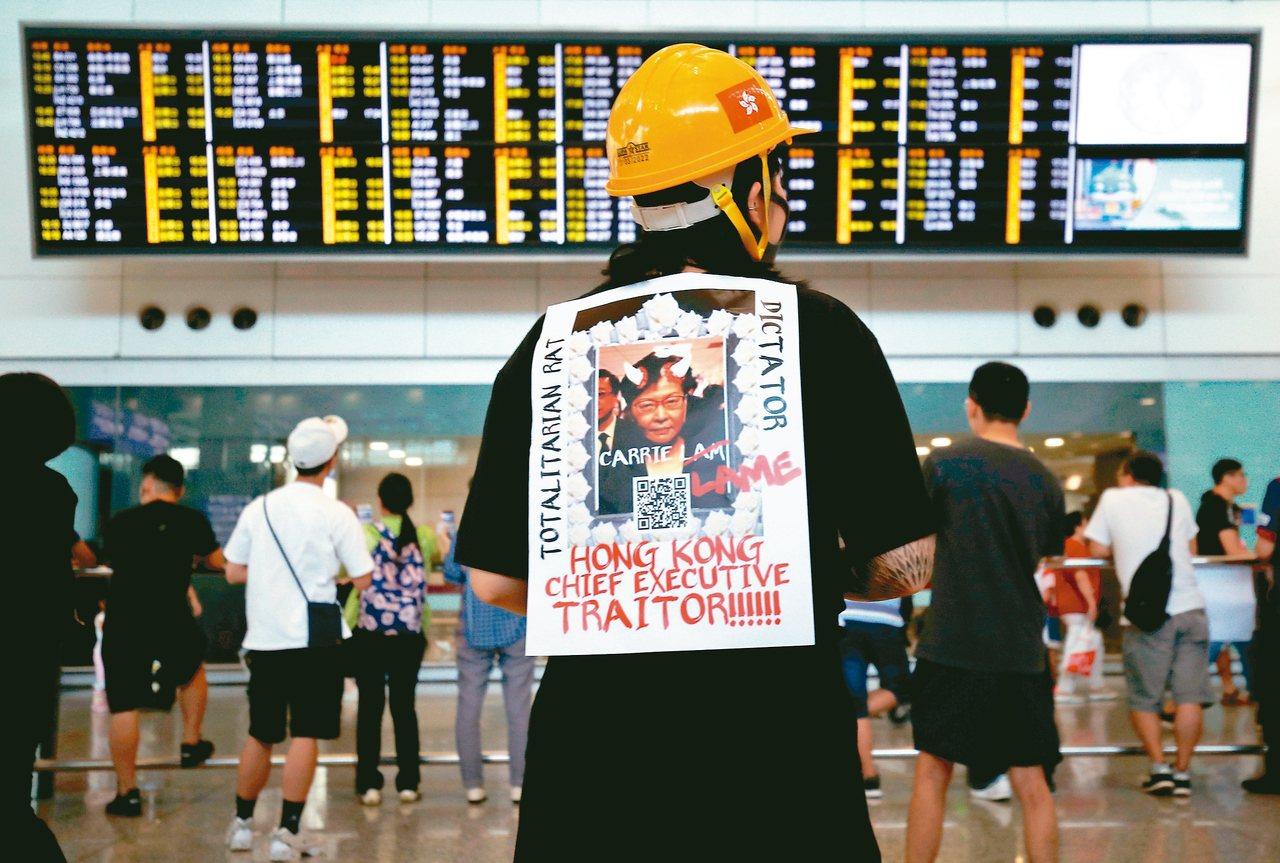 香港赤鱲角機場26日有示威者掛著標語牌抗議。 路透