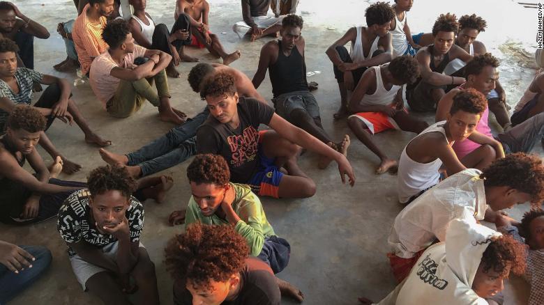 利比亞外海於25日發生船難,獲救的移民坐在海岸上。 圖擷自CNN