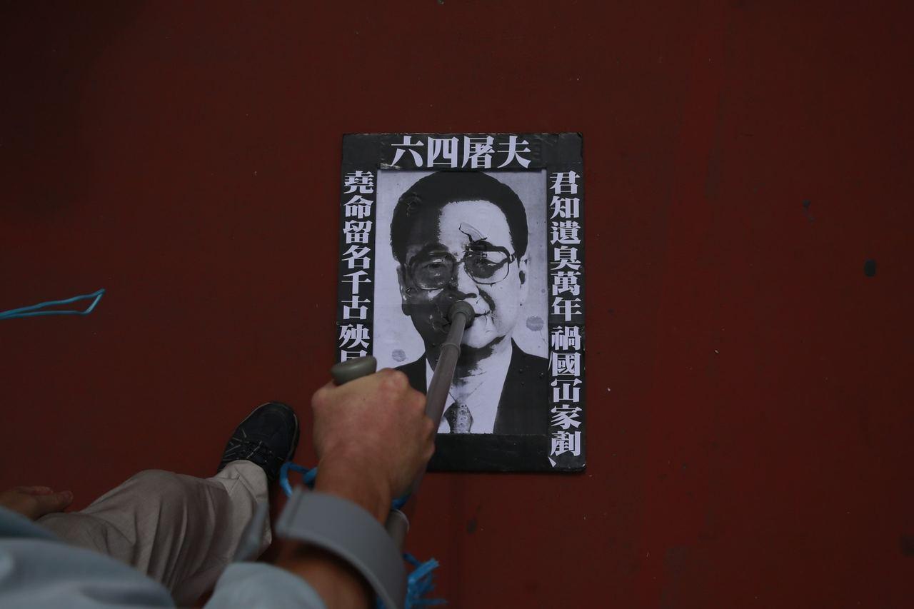 有市民將李鵬肖像海報放置在地上,讓途經市民會任意上前踐踏。 記者梁鵬威攝