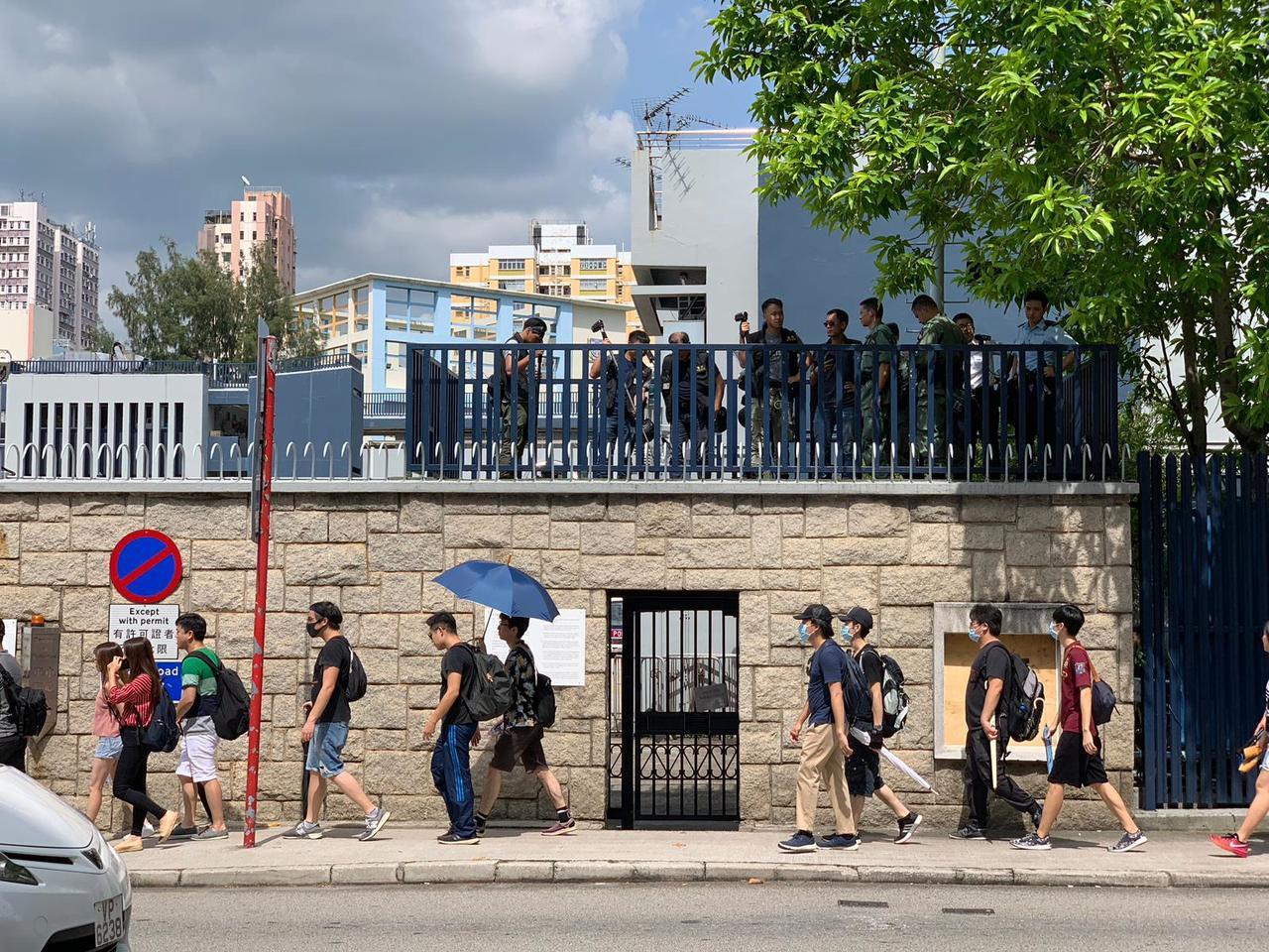 一批身穿黑衣、戴口罩和頭盔人士,午後陸續在元朗一帶聚集,當中部分人士手持雨傘。(...