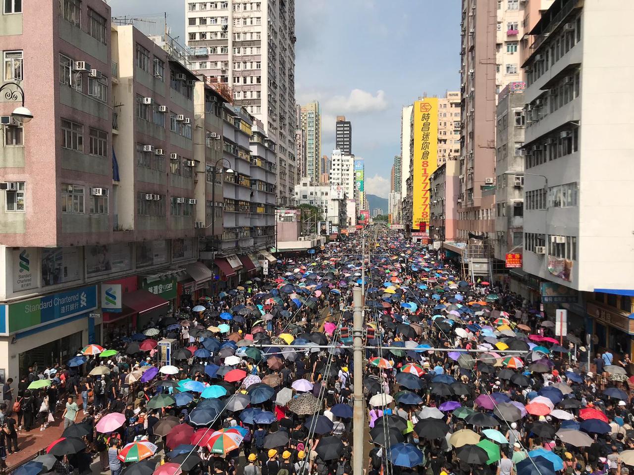 大批黑衣人在元朗廣場對出的大馬路行車線上遊行。(星島網)
