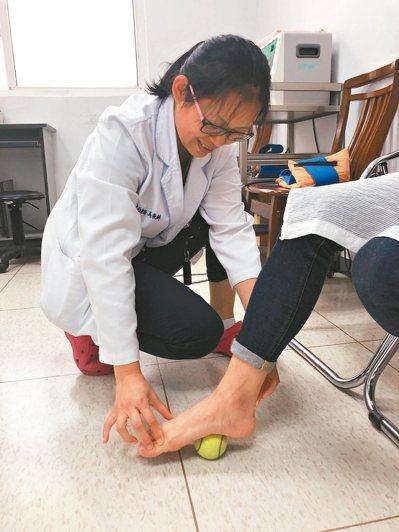 居家保養可以訓練肌力和伸展,如用網球踩在腳底等。 記者游明煌/攝影