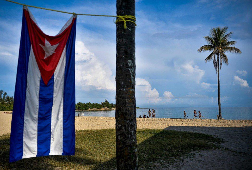 一面古巴國旗掛在巴庫蘭瑙海灘,古巴憲法規定海灘屬於所有人。(法新社)