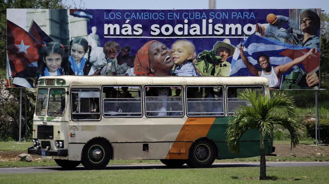 一輛巴士經過哈瓦那街頭。不少古巴民眾連搭車到海灘的車費都負擔不起。(路透)