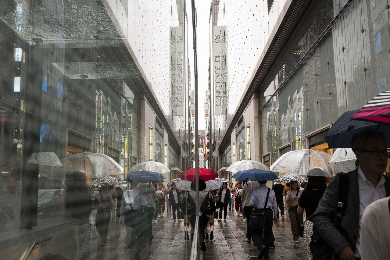 日本東京銀座,上班族撐傘走在街上。 美聯社
