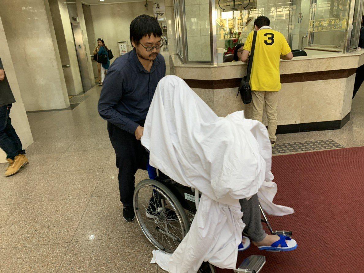 黃琪今天以白布遮臉、坐輪椅出庭。記者王聖藜/攝影