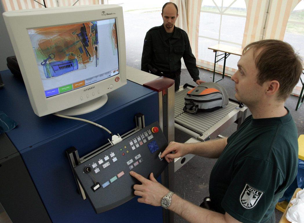 德國一名海關人員以X光機掃描旅客托運行李。 (法新社)
