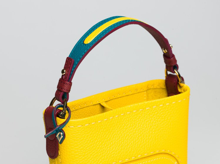 Pin系列芒果黃手袋的提把,撞色拼接皮革做工細緻。圖/DELVAUX提供