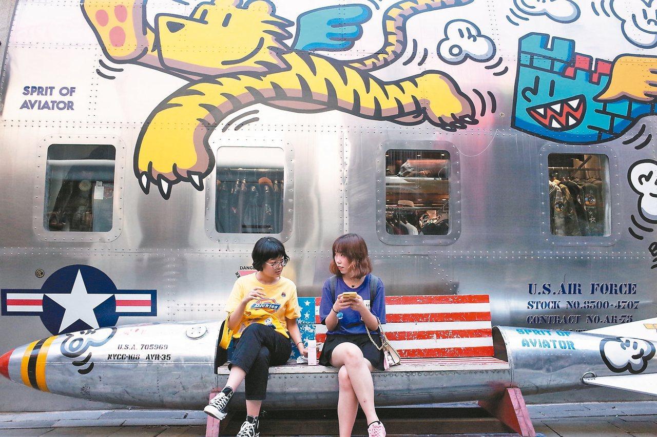 美中貿易戰再度升溫,台灣經濟如洗三溫暖;圖為北京年輕人坐在塗有美國星條旗的飛彈造...