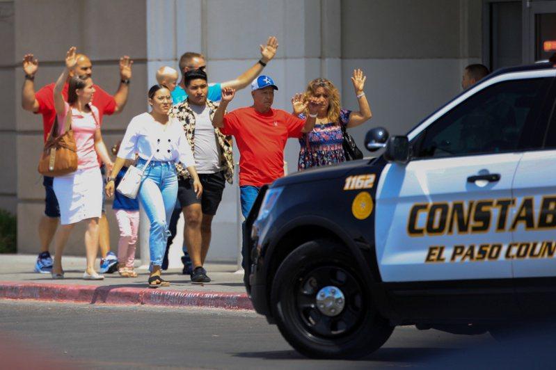 槍擊案發生後,沃爾瑪的顧客高舉雙手走出賣場。 路透