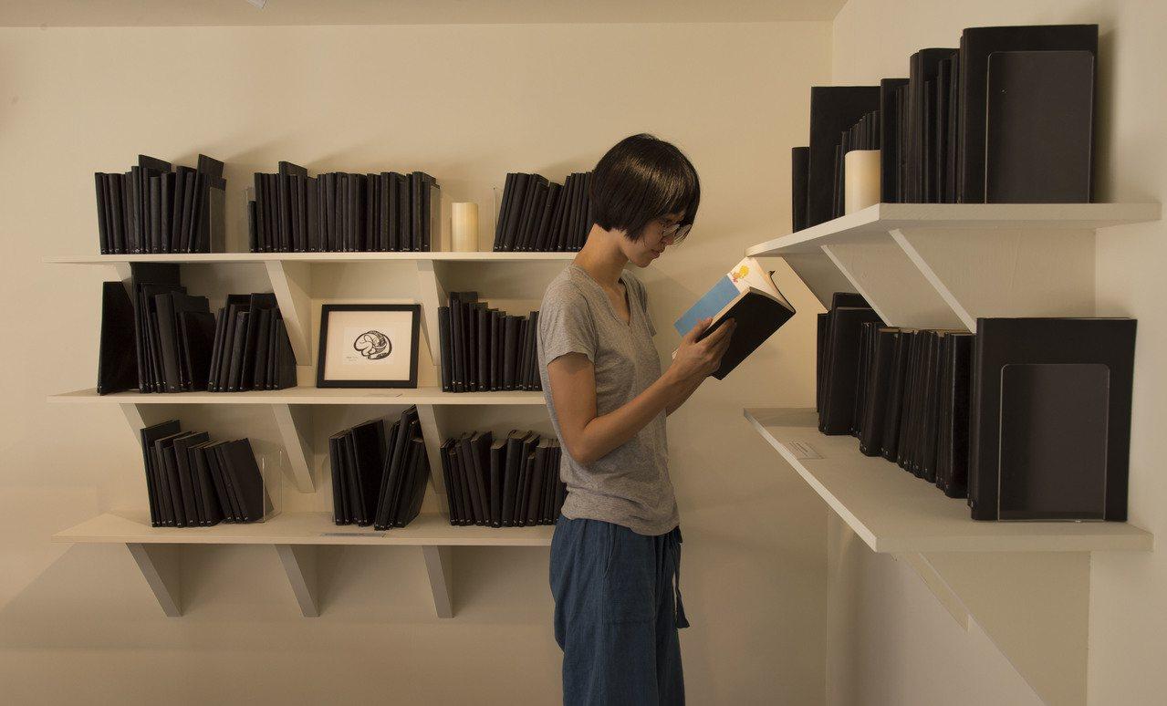 台北當代藝術館推出「遠方的書間」,邀請觀眾在未知的狀態下,親自翻閱每一本包著黑色...