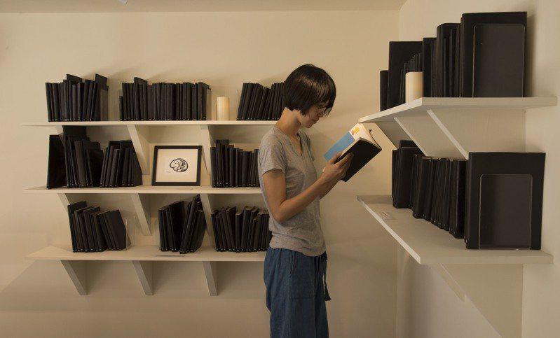 台北當代藝術館推出「遠方的書間」,邀請觀眾在未知的狀態下,親自翻閱每一本包著黑色封套的書後,才能知曉書本內容。圖/台北當代藝術館提供