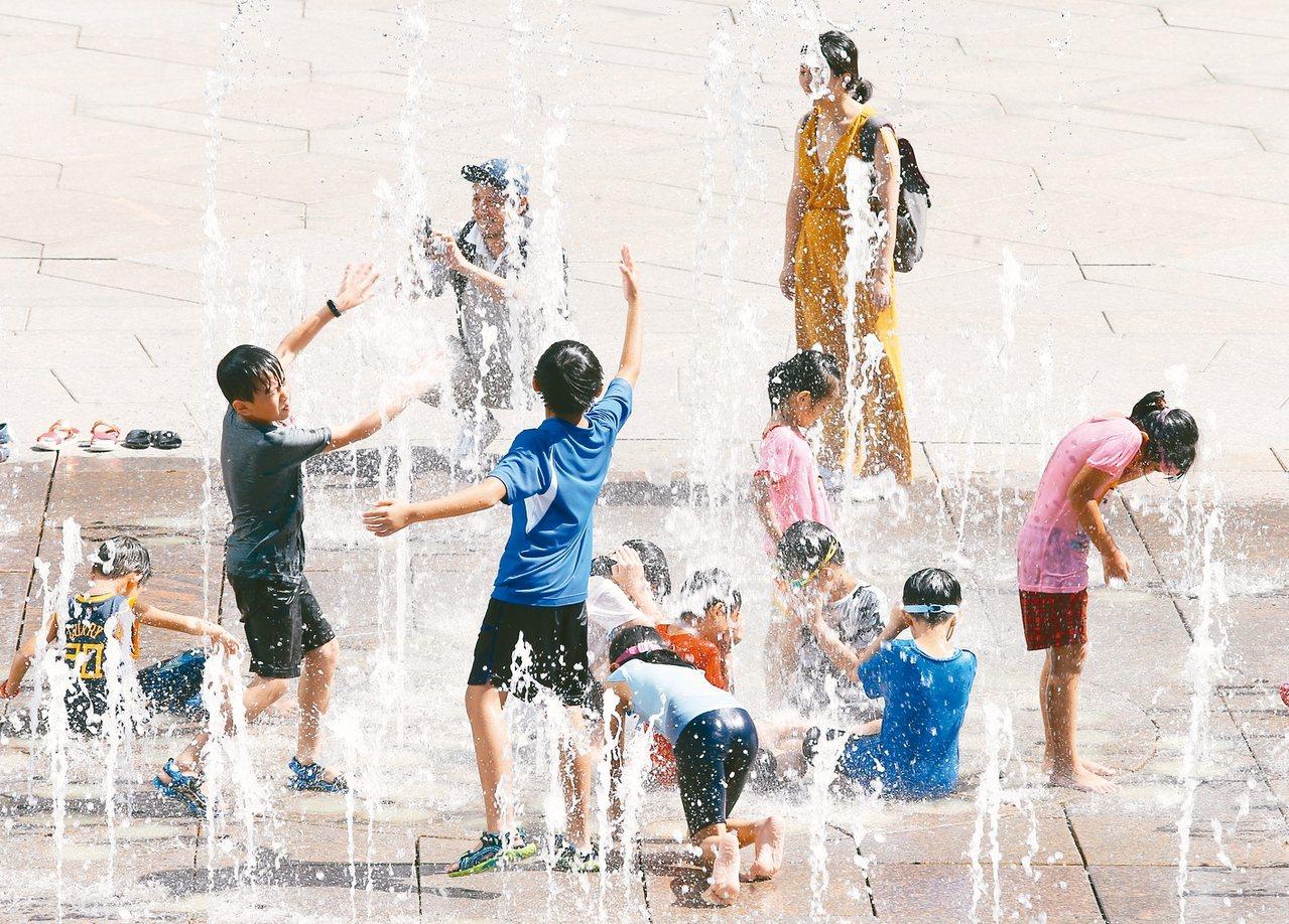 各地連日高溫,圖為台北101大樓旁噴水廣場上的小朋友開心玩水消暑。 圖╱聯合報系...