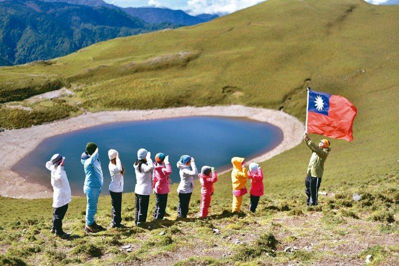 在有「天使的眼淚」之稱的嘉明湖畔,日前舉行了一場特別的升旗典禮。一家十口包含六大四小的登山隊,其中最小的只有8歲,在清晨的強風低溫中,列隊站在海拔3310公尺的嘉明湖邊高唱國歌,禮成後並高喊「我愛中華民國」。 圖/詹惠萌提供