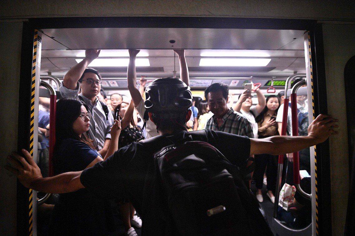 8月5日在港鐵砲台山站。示威者阻擋地鐵門關上。針對癱瘓交通的行動響應,分為香港本...