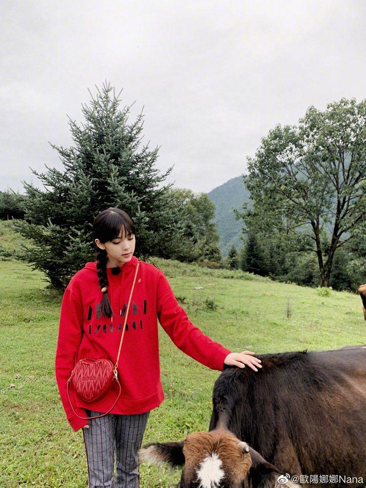 歐陽娜娜穿上Armani Exchange秋冬系列紅色連帽Logo上衣,搭配灰色...