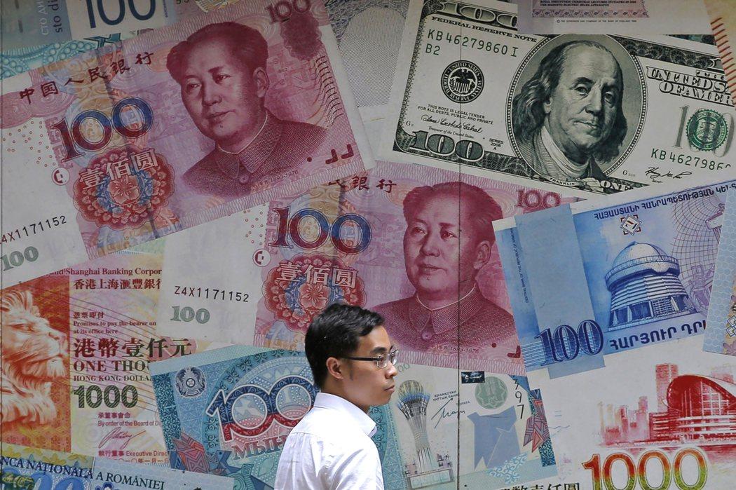 圖為男子經過香港中環一面以人民幣圖案裝飾的牆。(美聯社)