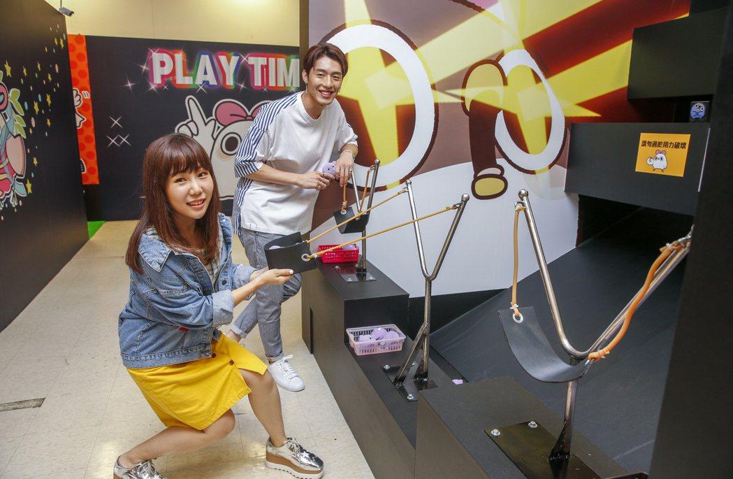 黃昺翔(左)與魏妙如(右)下午一起前去看「懶得鳥你」展覽,兩人玩起射擊遊戲。記者...