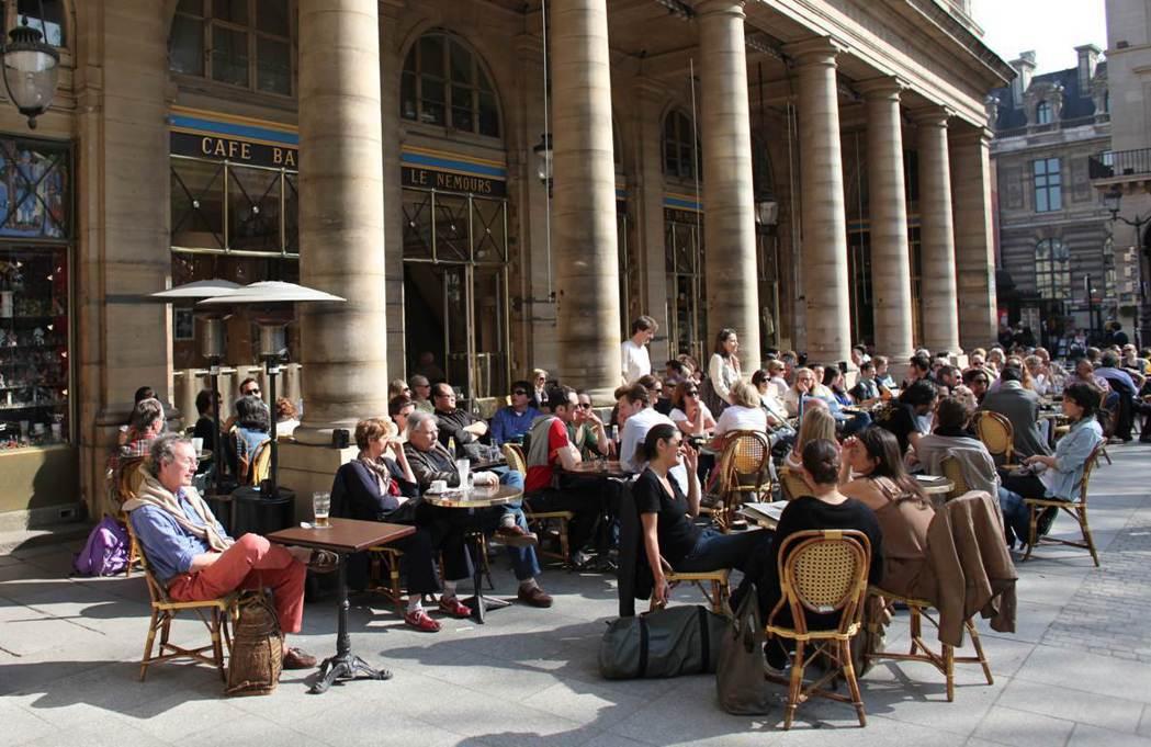 天氣再熱,巴黎人還是喜歡傾巢而出,讓露天咖啡店的座位區一位難求。 圖/歐新社