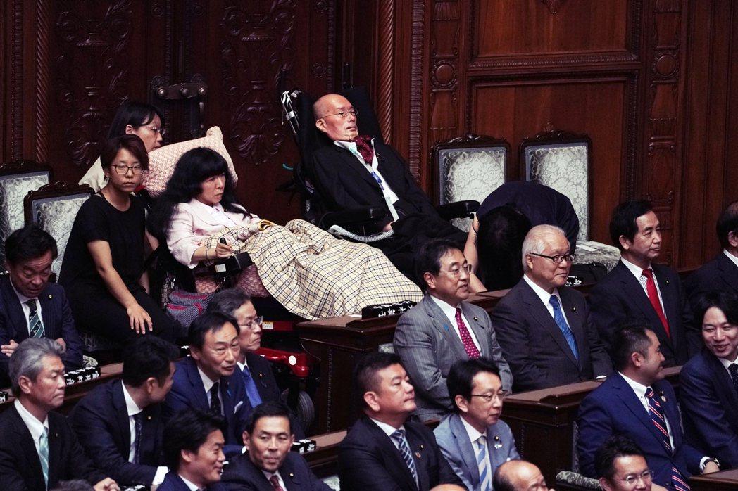 參議院內的木村英子與船後靖彦,身後則是看護員。船後靖彦近日則提議,希望能在議場中...